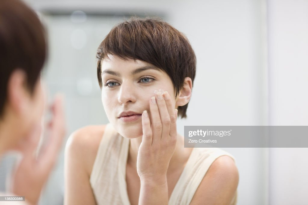 Woman applying moisturizer in mirror : Stock Photo