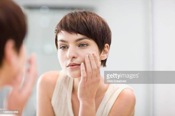 woman applying moisturizer in mirror - woman in mirror stock photos and pictures