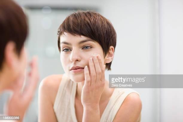 woman applying moisturizer in mirror - só uma mulher jovem imagens e fotografias de stock