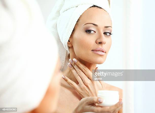 Woman applying moisturizer onto her neck