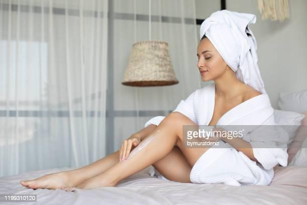 vrouw die moisturizer aanbrengt - erotische massage stockfoto's en -beelden