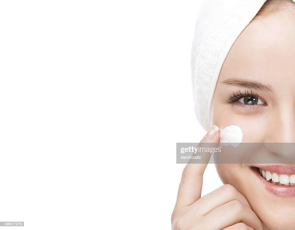 Woman applying moisturizer : Stock Photo