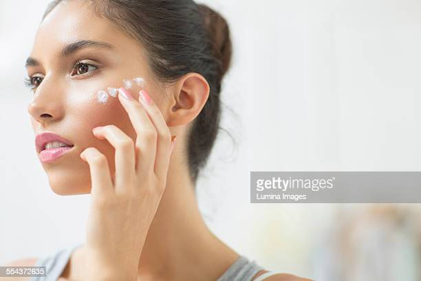 woman applying moisturizer to cheek - wrinkled stock pictures, royalty-free photos & images