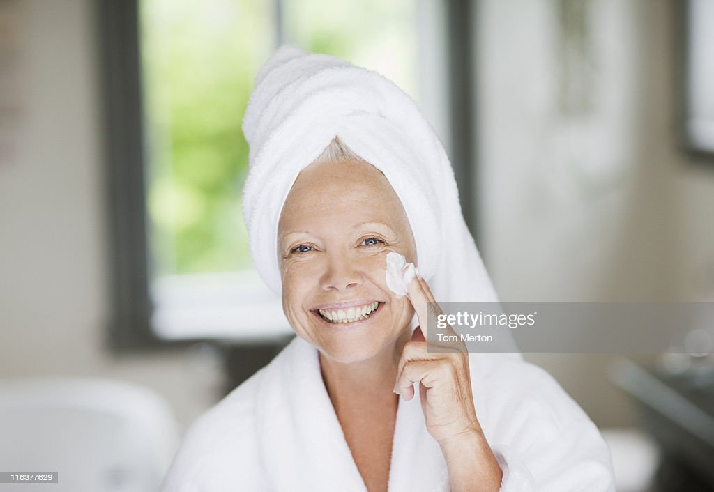 Woman applying moisturizer to face : Stock Photo