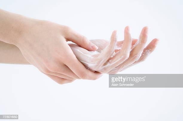 Woman applying moisturizer to hand, close up (studio)