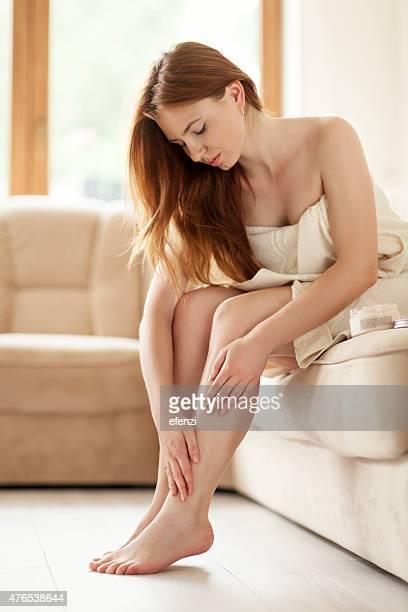 Frau Anwendung Feuchtigkeitscreme auf die Beine