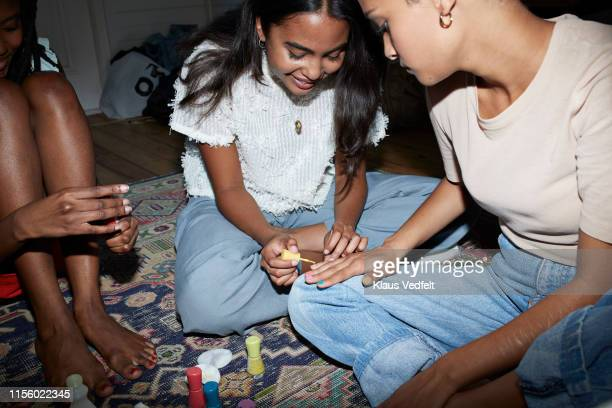 woman applying nail polish on friend's nails - only young women stock pictures, royalty-free photos & images