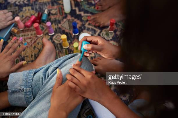 woman applying nail polish to friend - part of a series foto e immagini stock