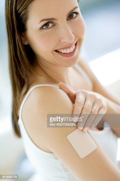 Woman applying nicotine patch, portrait