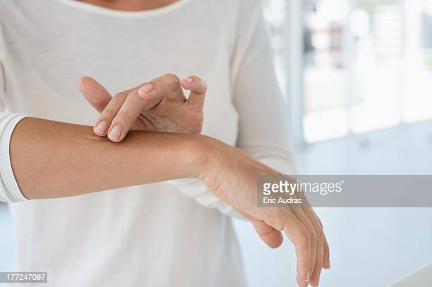 woman applying ointment on her arm - schimmelinfectie stockfoto's en -beelden