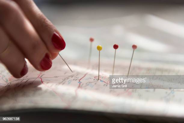 woman applying pins on map - stecknadel stock-fotos und bilder