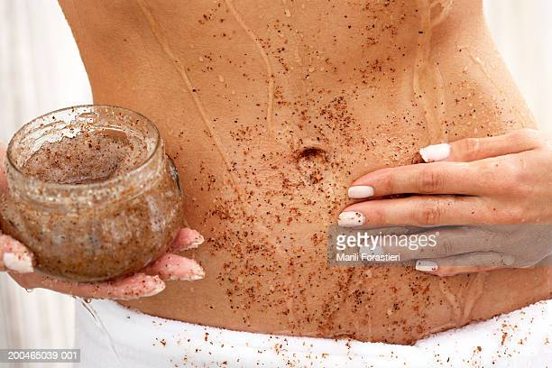 Woman applying scrub to abdomen, mid section, close-up