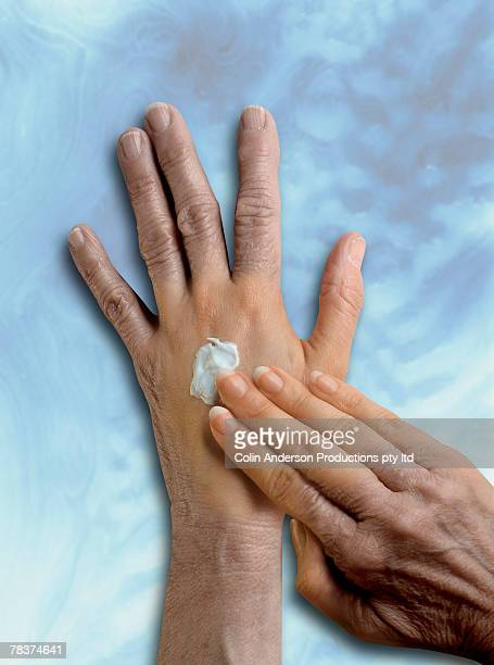 Woman applying skin cream on hands