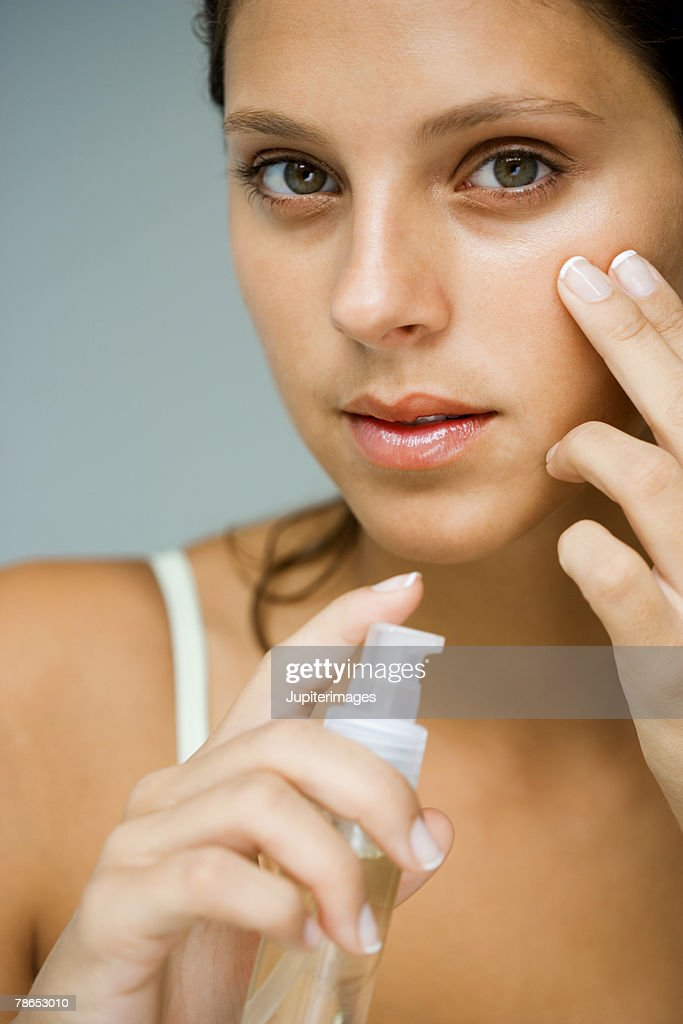 Woman applying skin cream : Stock Photo