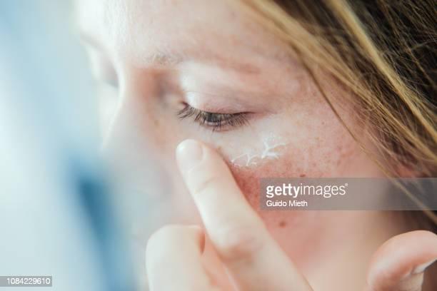 woman applying skin face cream. - creme stock-fotos und bilder
