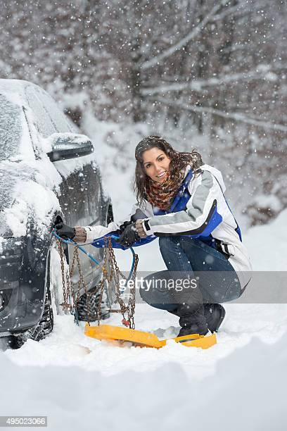 Woman applying Snow Chains, Heavy Snow Fall