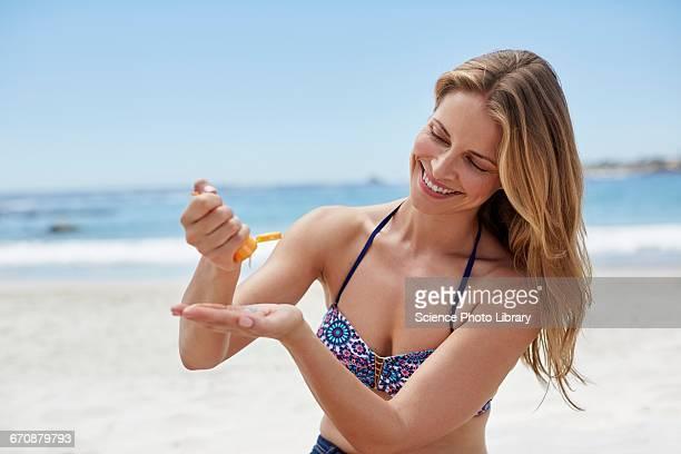 Woman applying sun cream on beach