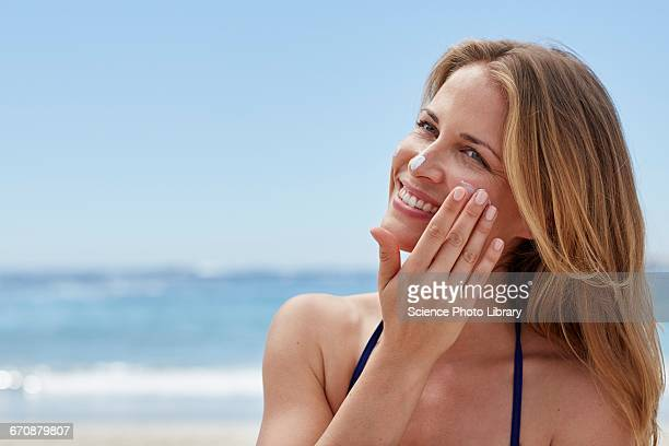 Woman applying sun cream on beach