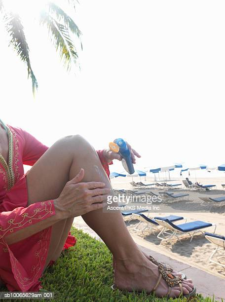 Woman applying sun cream on leg, low section