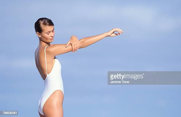 woman applying sunscreen at beach - cellulite foto e immagini stock