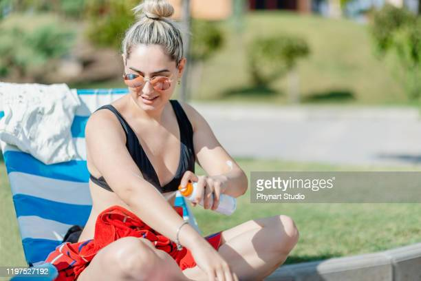 woman  applying sunscreen on arm - uv protection stock pictures, royalty-free photos & images