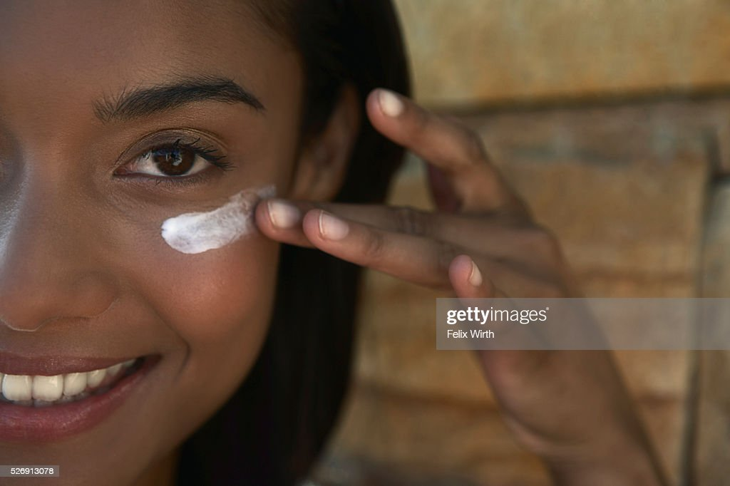 Woman applying sunscreen : Stock Photo