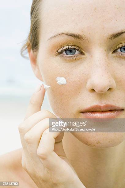 Woman applying sunscreen to face, close-up