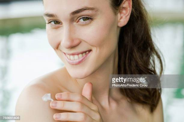 woman applying sunscreen to shoulder - beautiful bare breasted women stock pictures, royalty-free photos & images