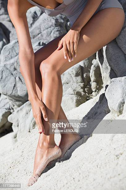 woman applying suntan lotion on her leg on the beach - jolies jambes photos et images de collection