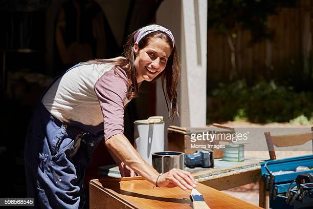 Woman applying varnish wooden furniture