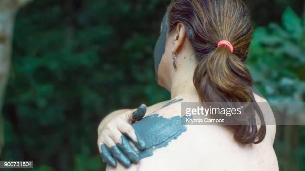 Woman Applying Volcanic Mud Treatment on shoulders