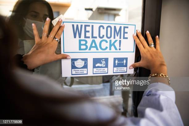 "woman applying ""welcome back"" sign to the school entrance - reopening stock pictures, royalty-free photos & images"