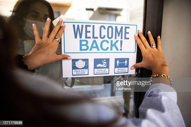 """mulher aplicando sinal de """"bem-vindo de volta"""" na entrada da escola - opening event - fotografias e filmes do acervo"""