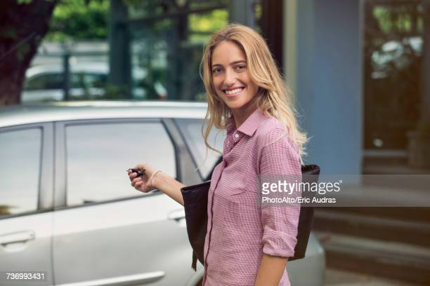 woman approaching car with key in hand, smiling over shoulder - 接近する 女性 ストックフォトと画像