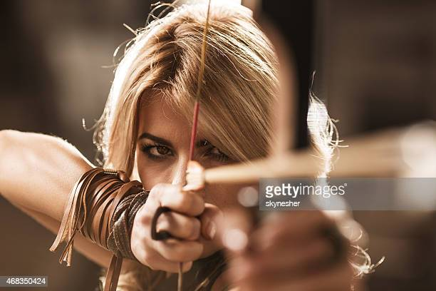 woman archer aiming with bow and arrow. - warrior person stock photos and pictures