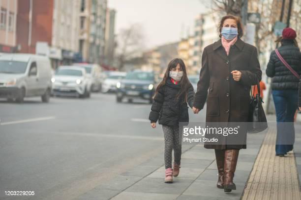 mulher vão trabalhar.ela usa máscara n95.prevenir pó e poluição pm2.5, mãe e filho usando uma máscara para proteger seu filho da poluição do ar e doenças infecciosas - mascara - fotografias e filmes do acervo