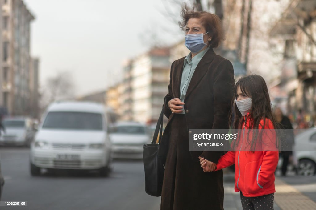 woman are going to work.she wears N95 mask.prevent PM2.5 dust and smog, mother and child wearing a mask to protect their child from air pollution and infectious diseases : Stock Photo