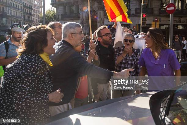 A woman argues with demonstrators after they block Gran Via street outside the Catalan VicePresident and Economy office as police officers hold a...