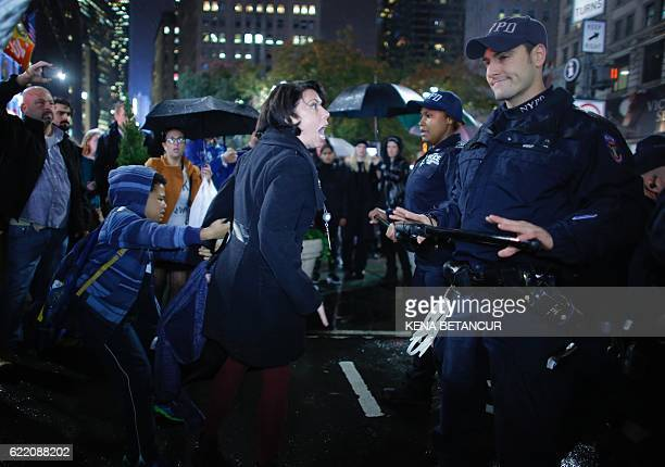 TOPSHOT A woman argues with NYPD officers as she takes part in a protest against Presidentelect Donald Trump in New York City on November 9 2016 /...