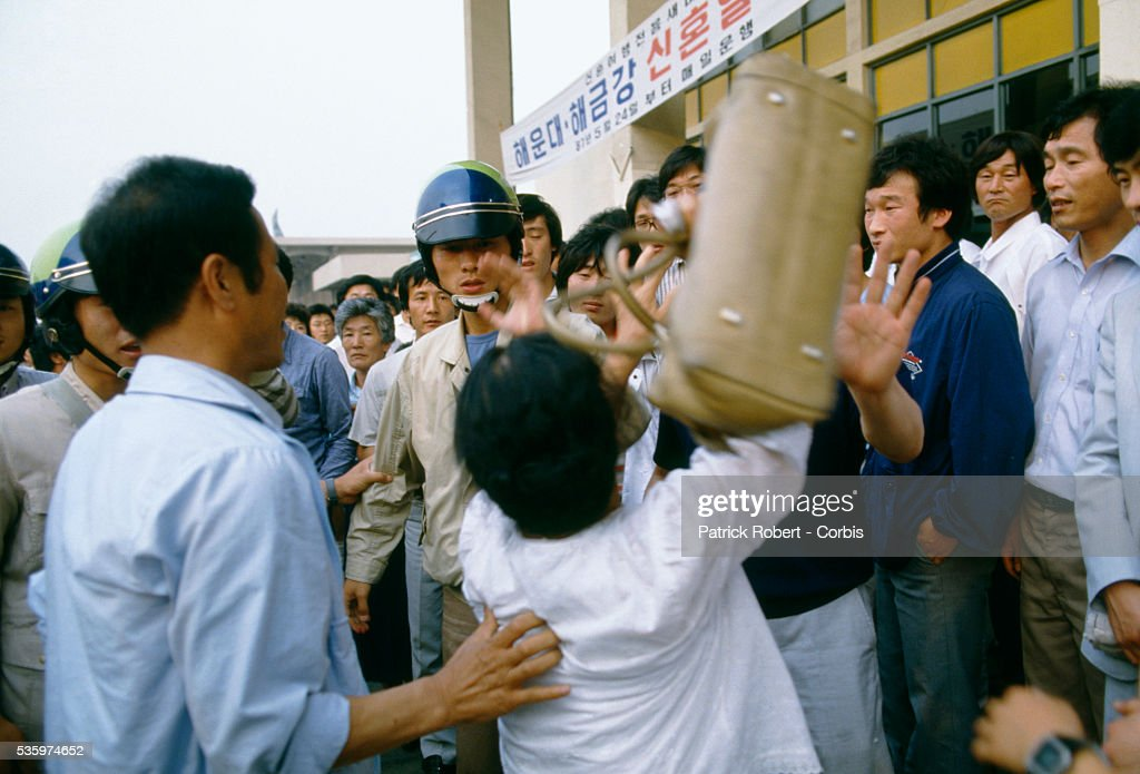 A woman argues with South Korean demonstrators who are holding a rally in support of pro-democracy leader Kim Dae-jung near Kim's home in Yongdong. Students and other demonstrators who joined them all over South Korea protested the political and economic situation and eventually brought the regime of President Chun Doo Hwan to an end. In October 1987, the National Assembly ratified a new constitution, which provided for direct presidential elections.