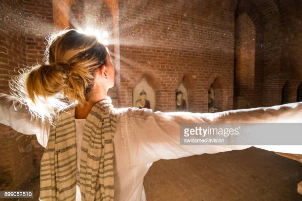 Woman arms outstretched in ancient temple, Myanmar