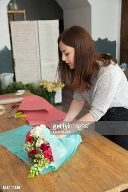 Woman arranging bouquet in paper