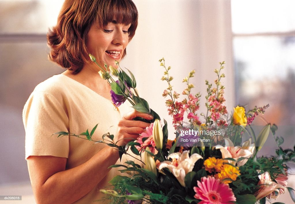 Woman arranging bouquet of flowers : Stock Photo