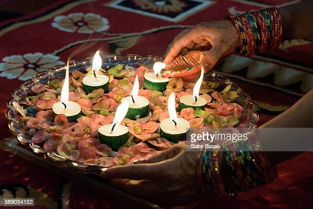 Woman arranging decorated diya/earthen lamps with flower on the eve of Diwali in traditional Indian ornaments.