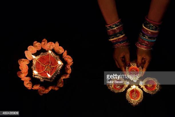 Woman arranging decorated earthen lamps,Diwali.