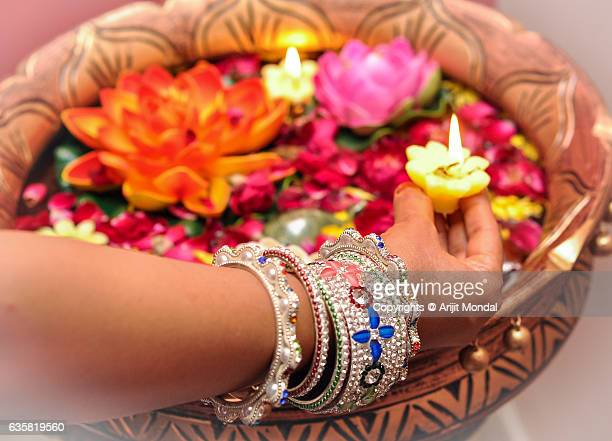 woman arranging decorated floating lamps with flower on the eve of diwali in traditional indian ornaments - diya oil lamp stock pictures, royalty-free photos & images