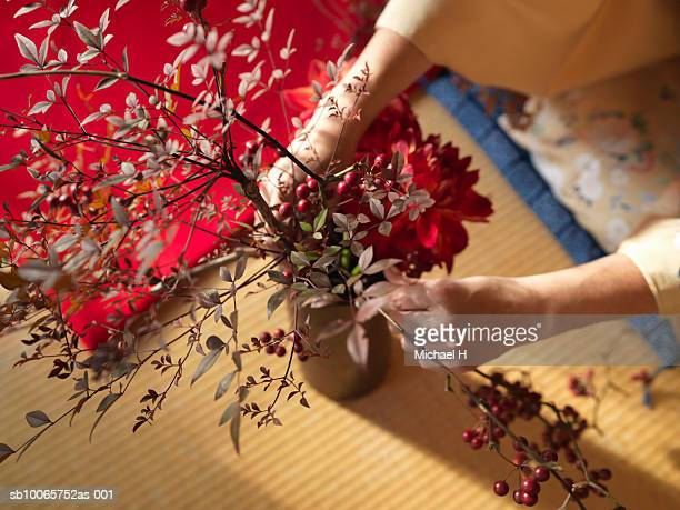 Woman arranging flowers, close up of hands