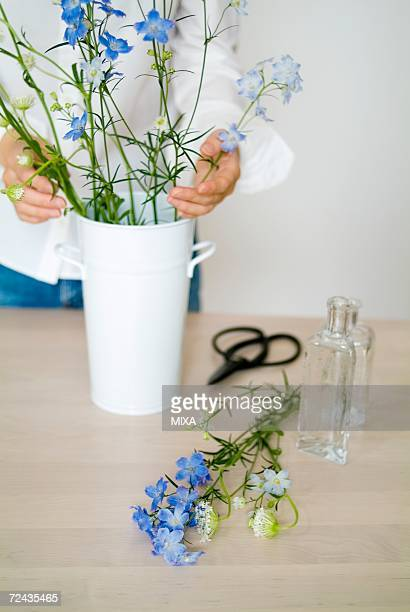 A woman arranging flowers in a vase