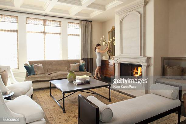 Woman arranging flowers in living room