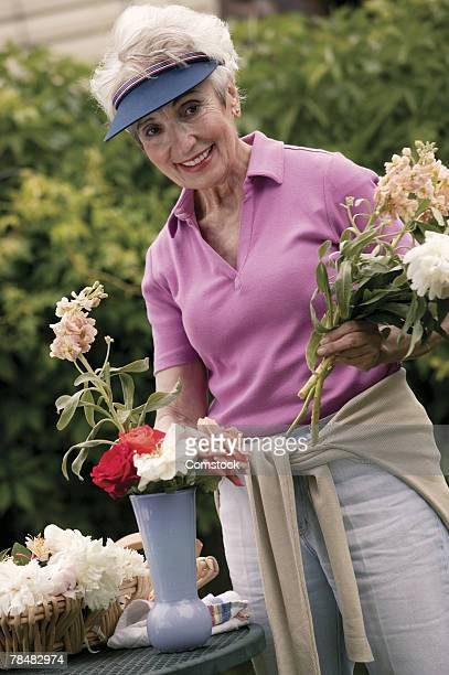 woman arranging flowers - inclinando se - fotografias e filmes do acervo